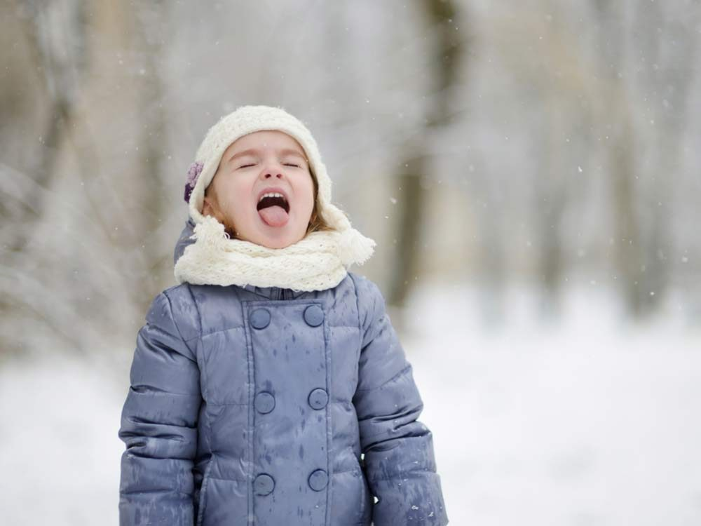 Young girl catching snowflakes in her mouth