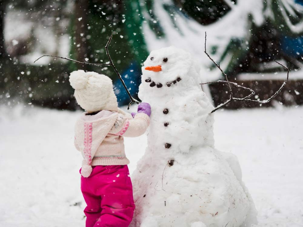 Toddler building a snowman