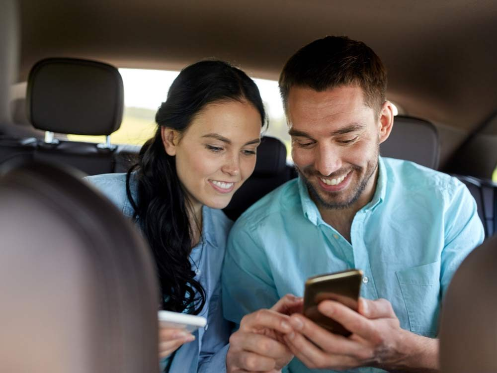 Man and woman passengers texting