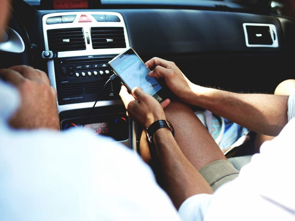 Friends texting in car while on road trip