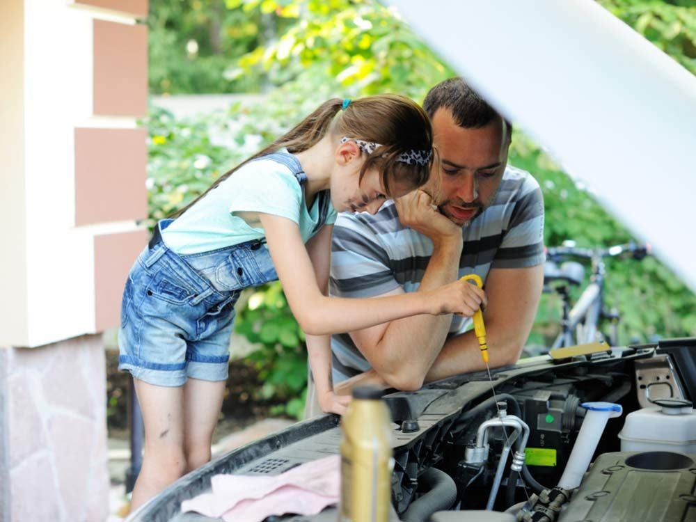 Father and daughter changing motor oil in car