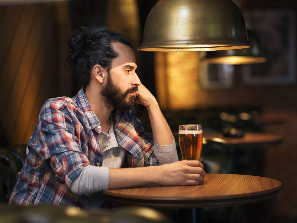 Lonely man drinking beer at bar