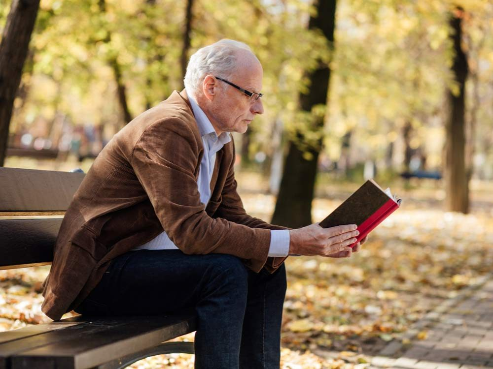 Middle-aged man reading book in the park
