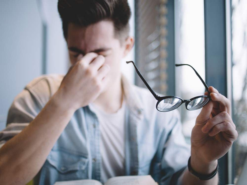 Young man removing his glasses