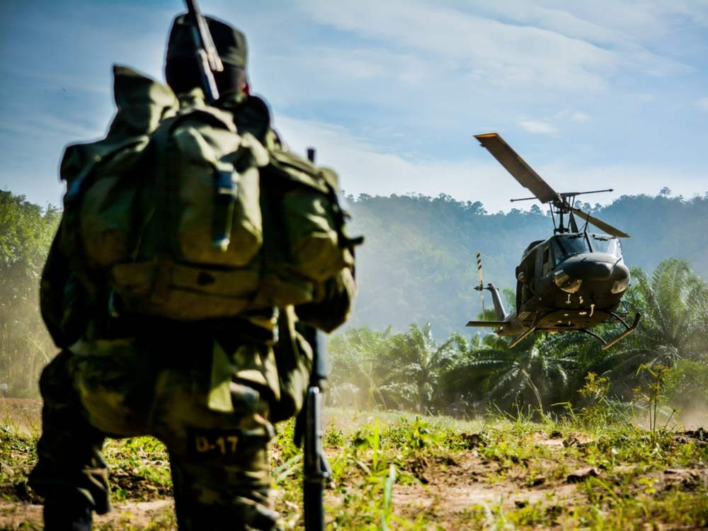Soldier watching helicopter in jungle
