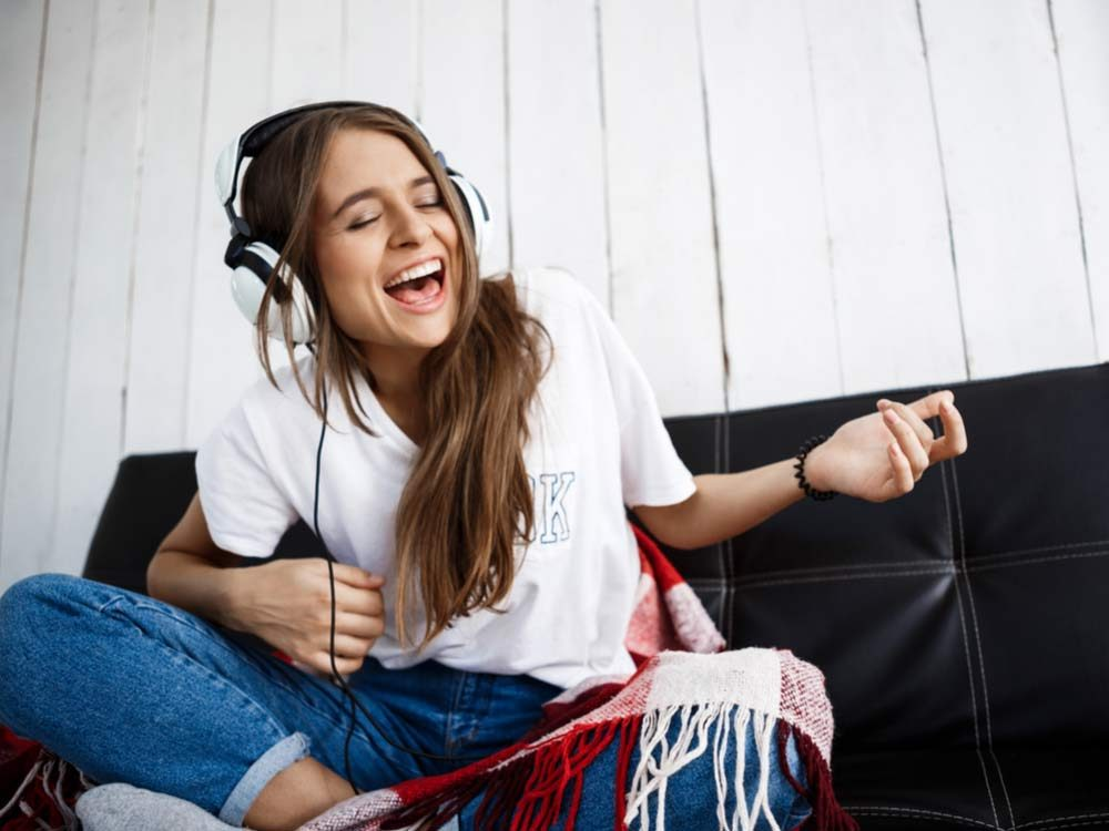 Woman sitting on couch listening to music on headphones