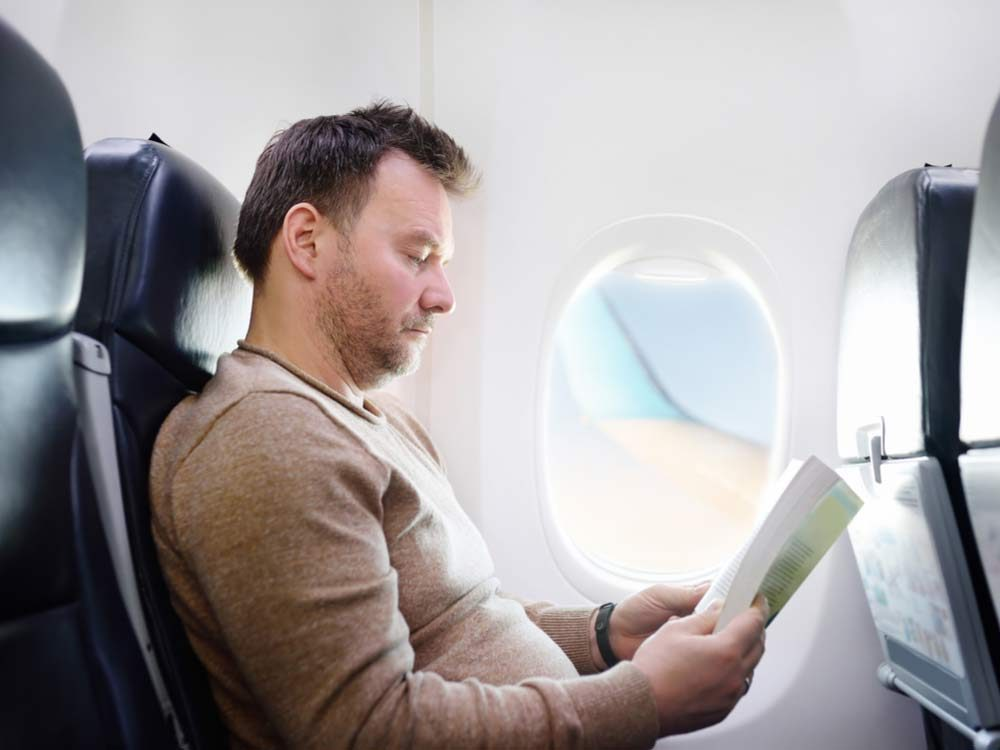 Man reading on airplane