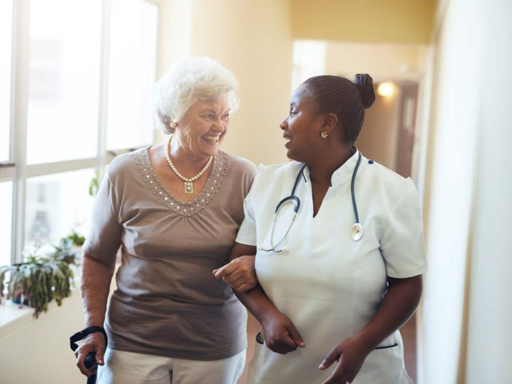 Elderly woman smiling with happy nurse