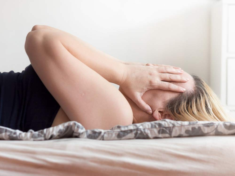 Stressed woman lying in bed