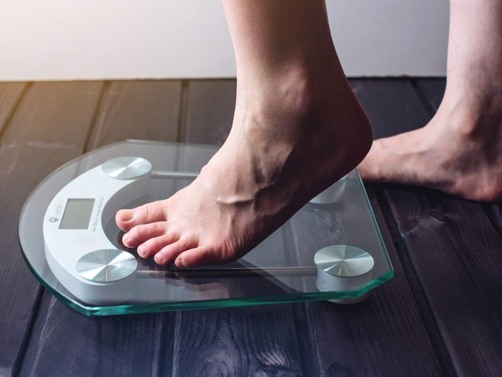 Female feet standing on weight scale