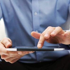 Man reading fake news on tablet