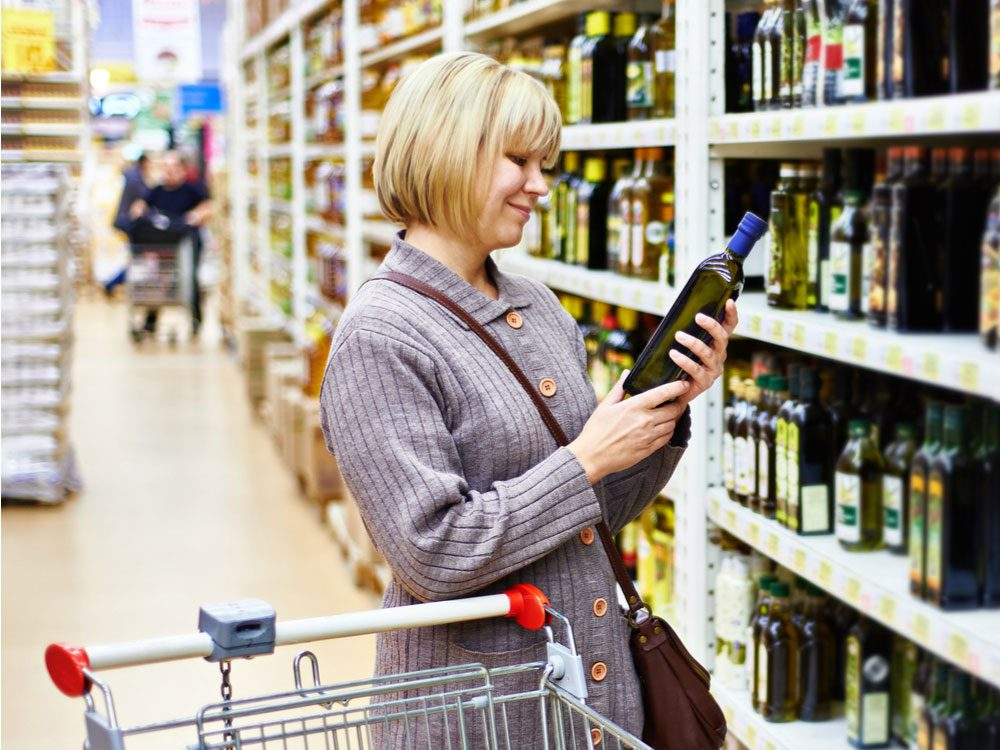 Woman buying canola oil in supermarket