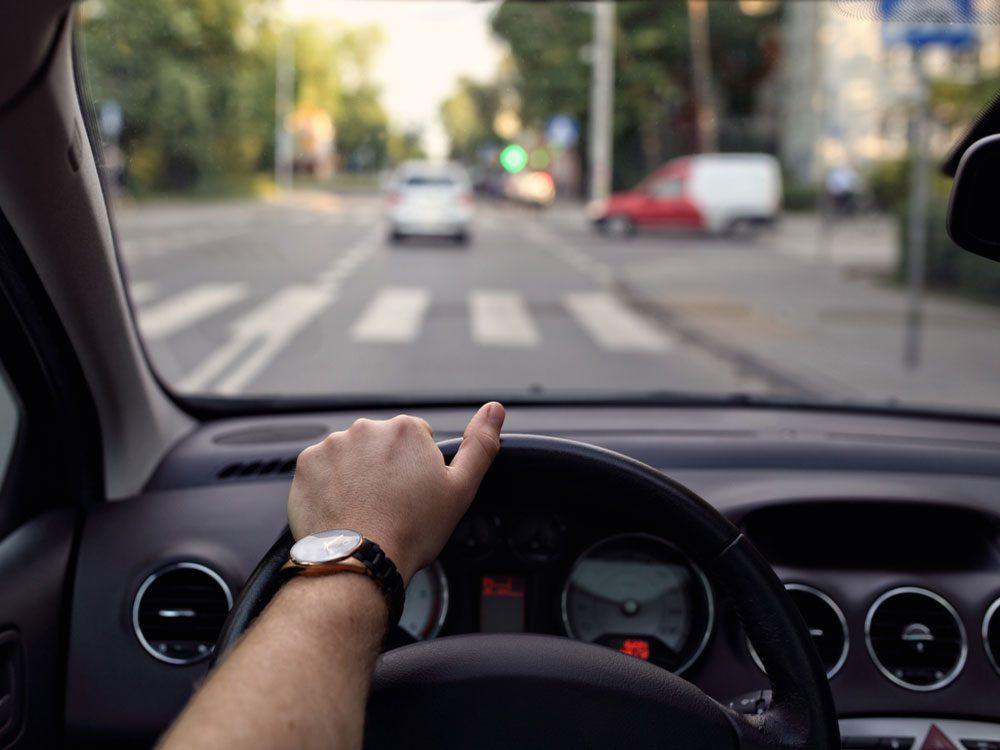 Male hands on steering wheel