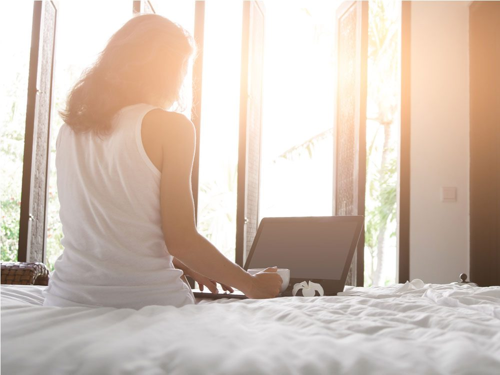 Woman using laptop in her hotel room