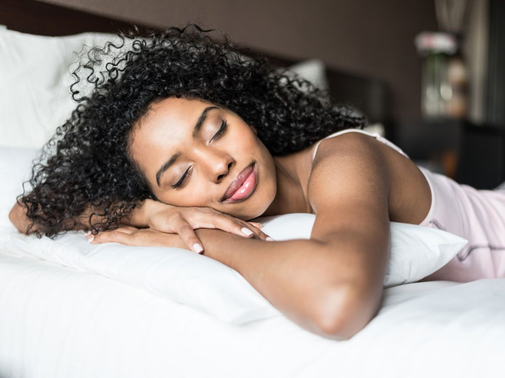 Happy woman sleeping on stomach