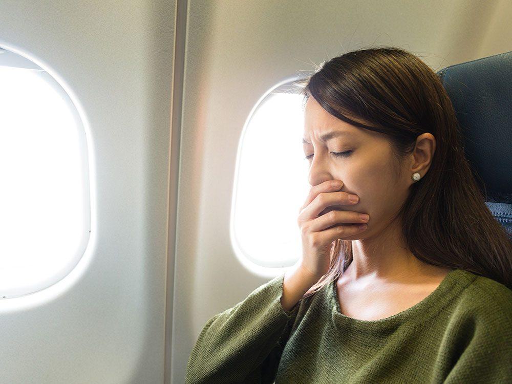 Woman feeling sleepy on plane