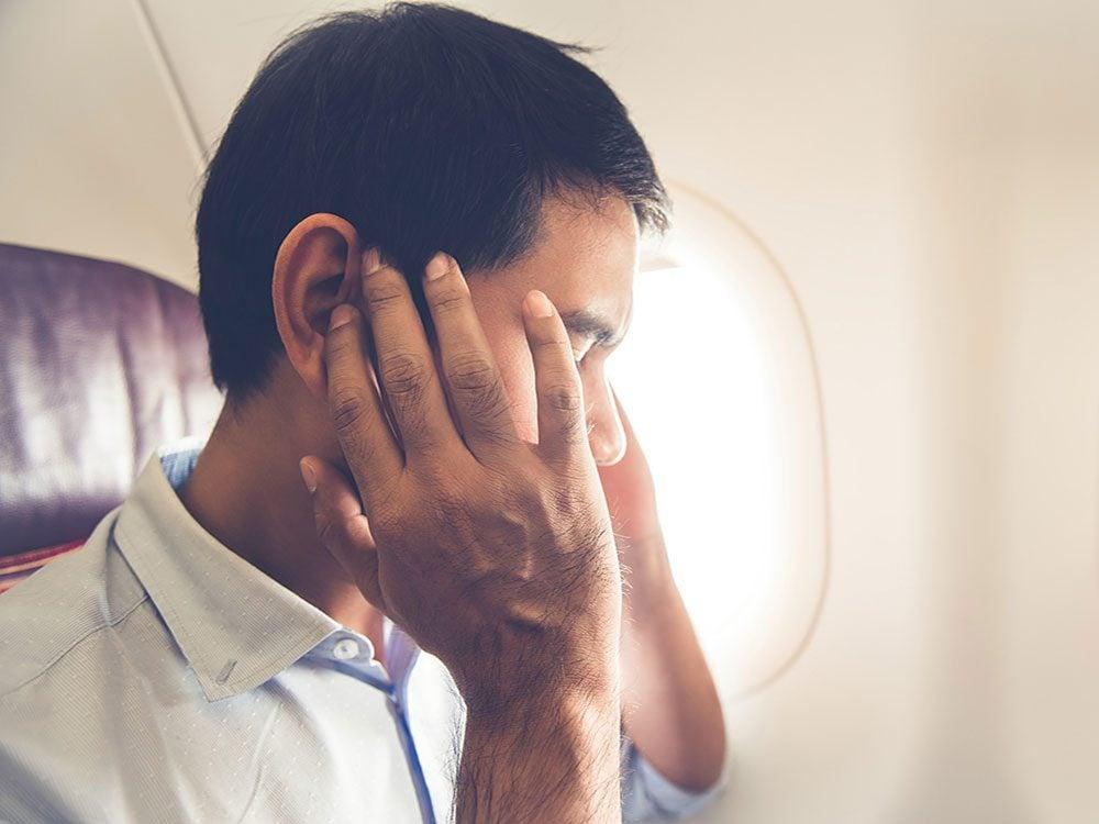 Man with headache on flight