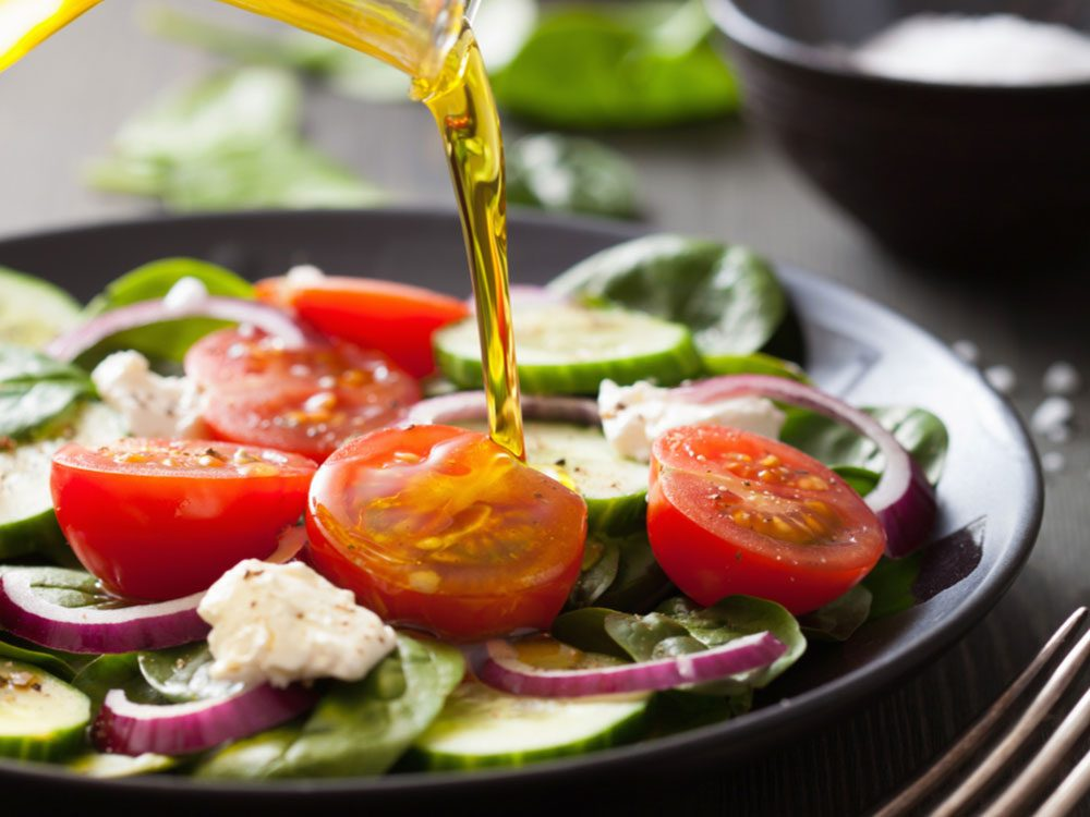 Pouring oil on garden salad