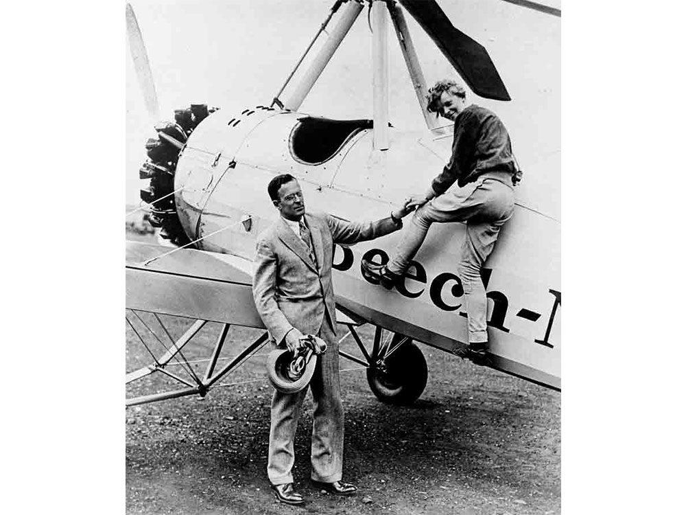 Amelia Earhart climbing into airplane