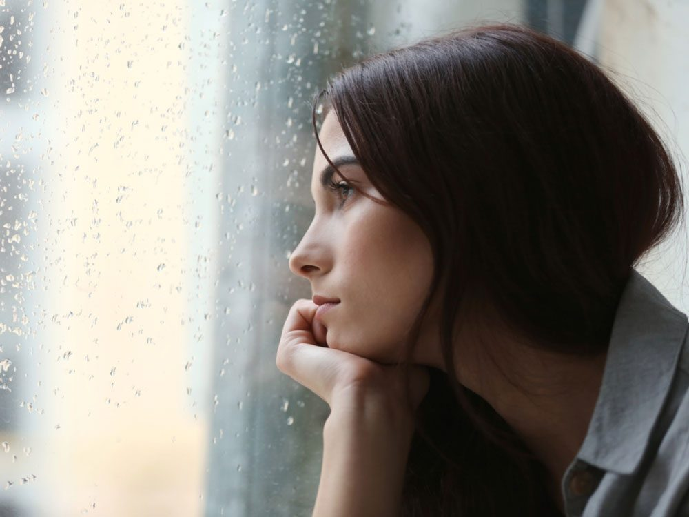 Contemplative woman looking out of rainy window
