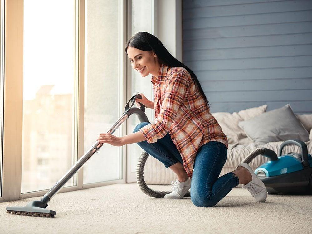 Woman vacuuming her living room