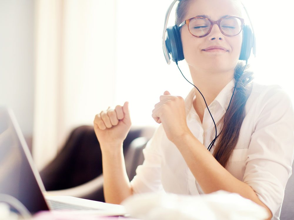 Woman happily listening to music at work