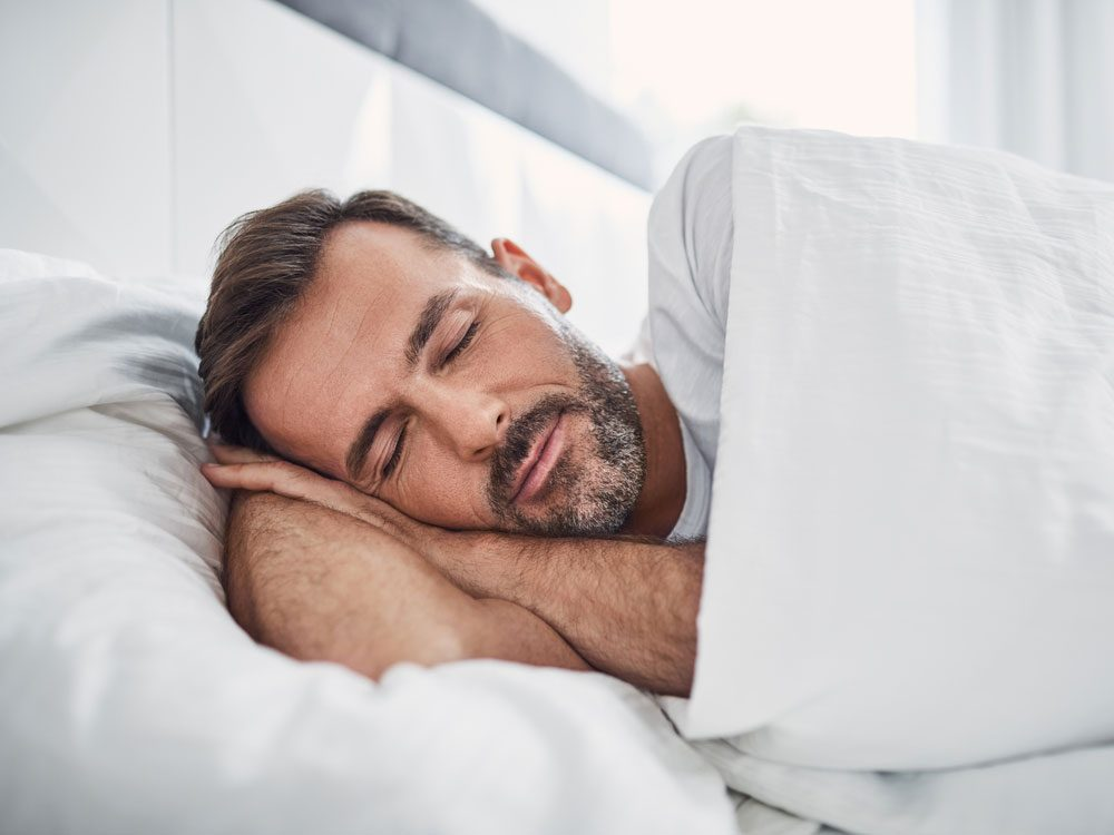 Bearded man sleeping in bed