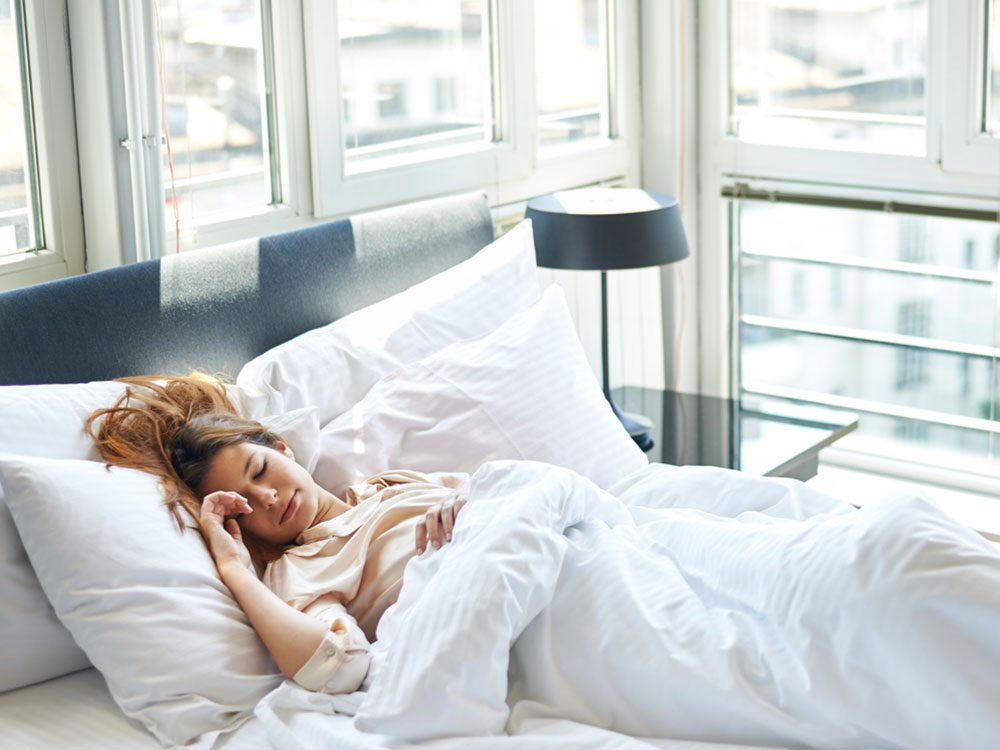 Woman waking up in hotel room bed
