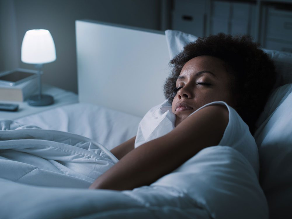 Woman sleeping with bedside lamp turned on