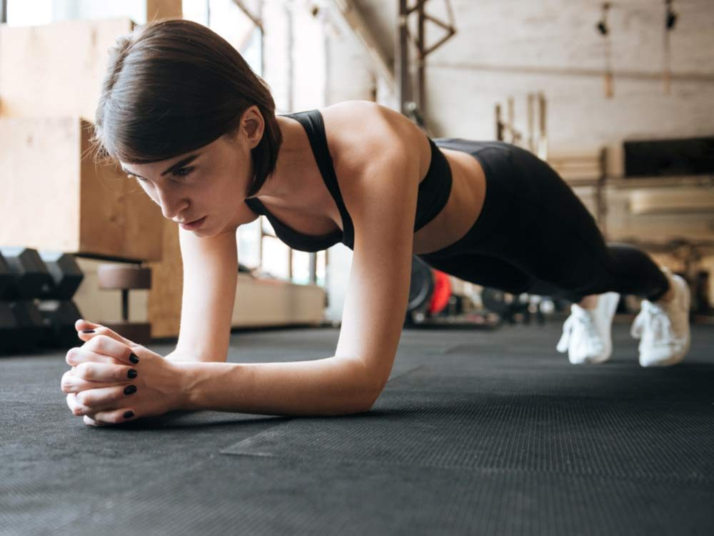Woman in plank position at the gym