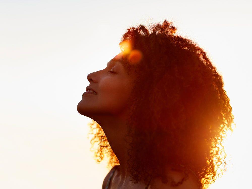 Smiling woman facing the sun