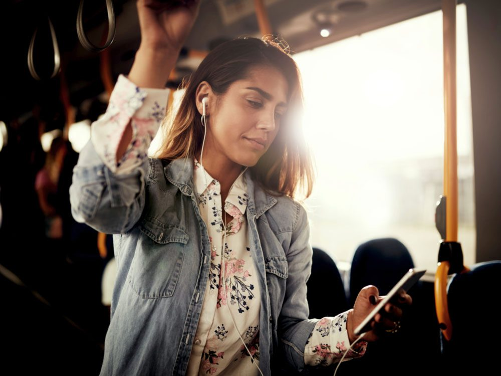 Attractive woman listening to music on the bus