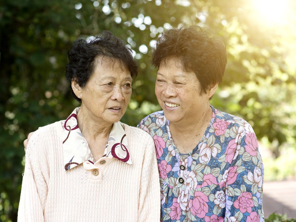 Two elderly Asian women talking to one another