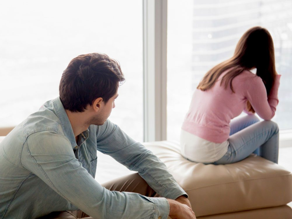 Young couple sitting in bedroom about to break up