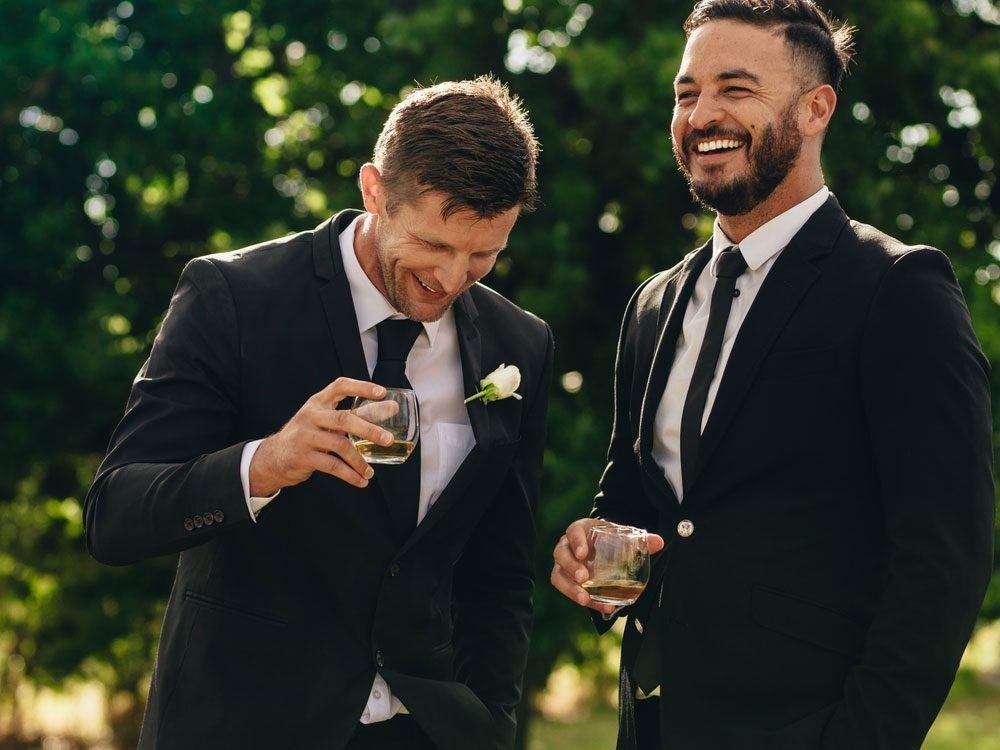 Groom and groomsman laughing at wedding