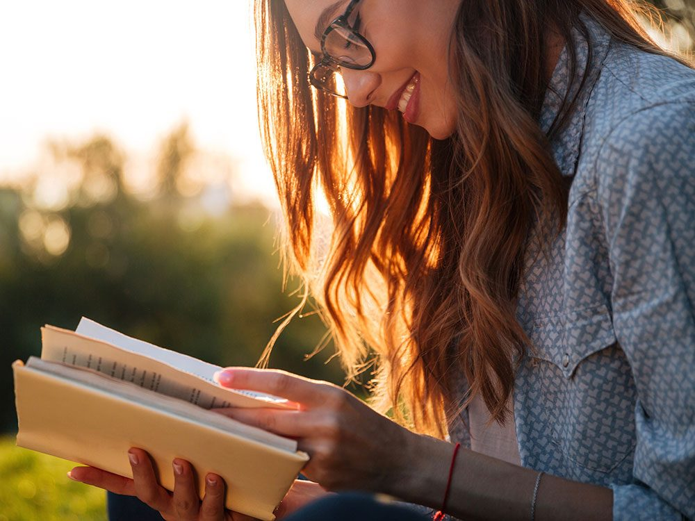 Brunette woman with glasses reading a book