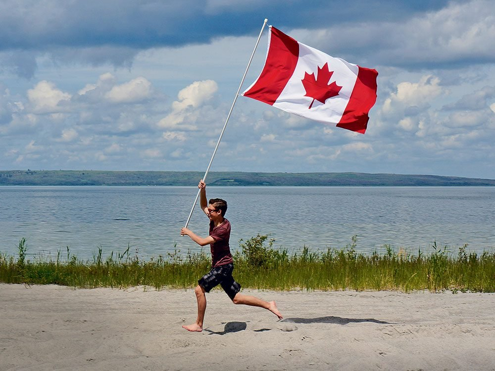 Canada Day: Boy running with Canadian flag