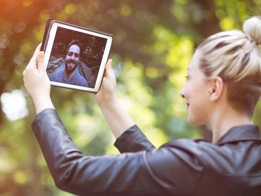 Couple in a long distance relationship talking to one another through a tablet