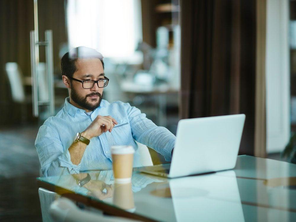 Asian man using laptop at cafe