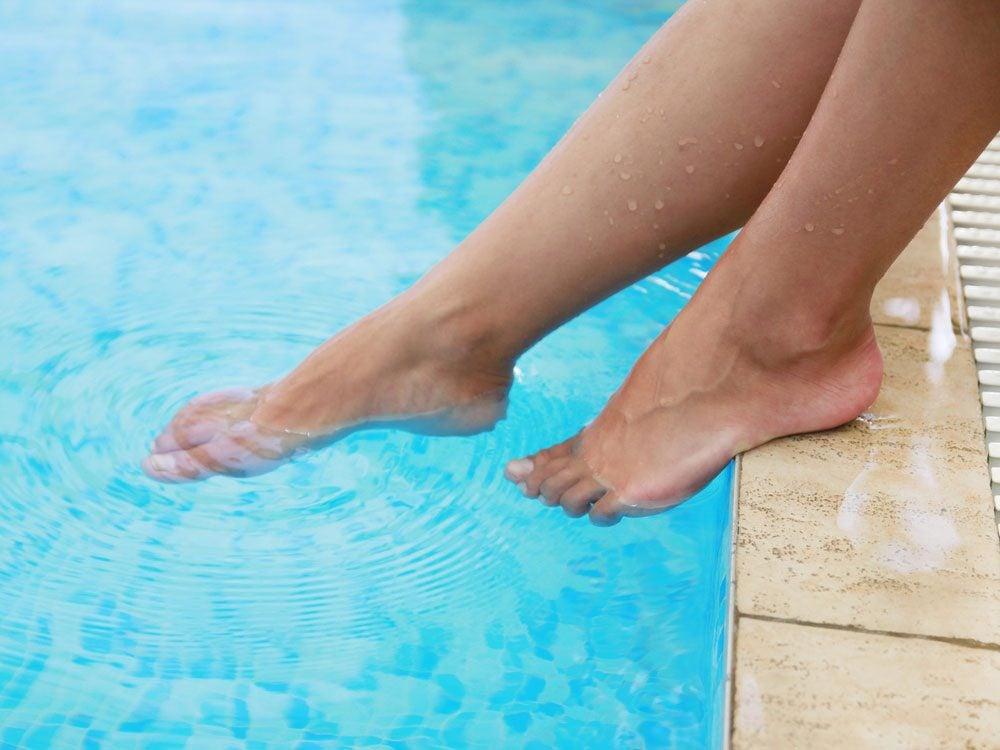 Woman putting her feet in pool