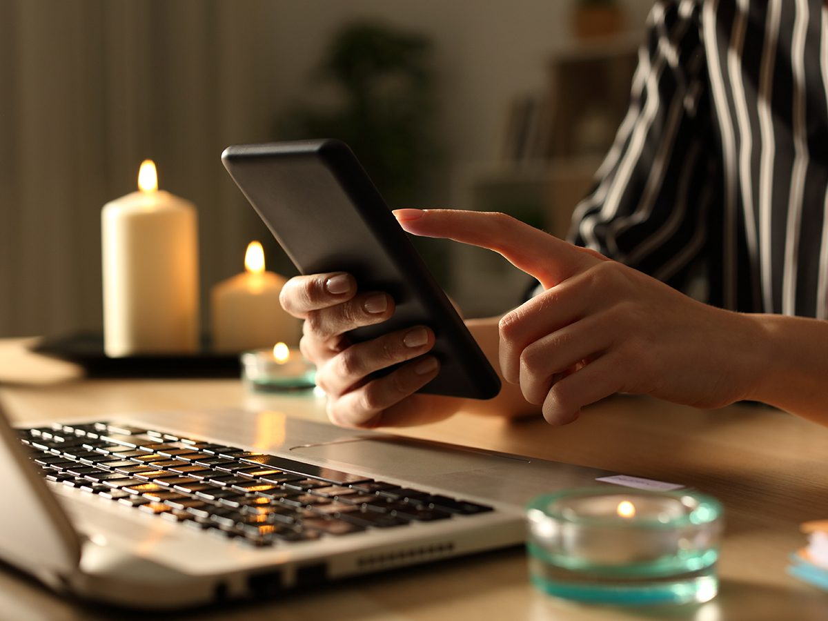 Close up of girl hands using smart phone on power outage with candles at night on a desk at home