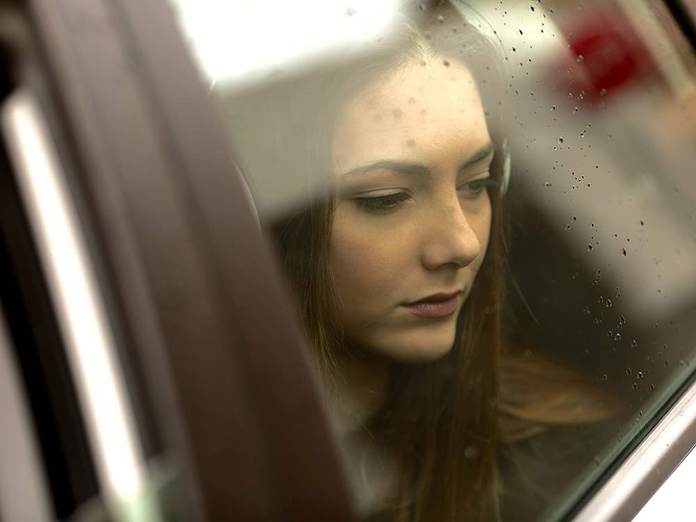 Sad woman looking through window on a rainy day