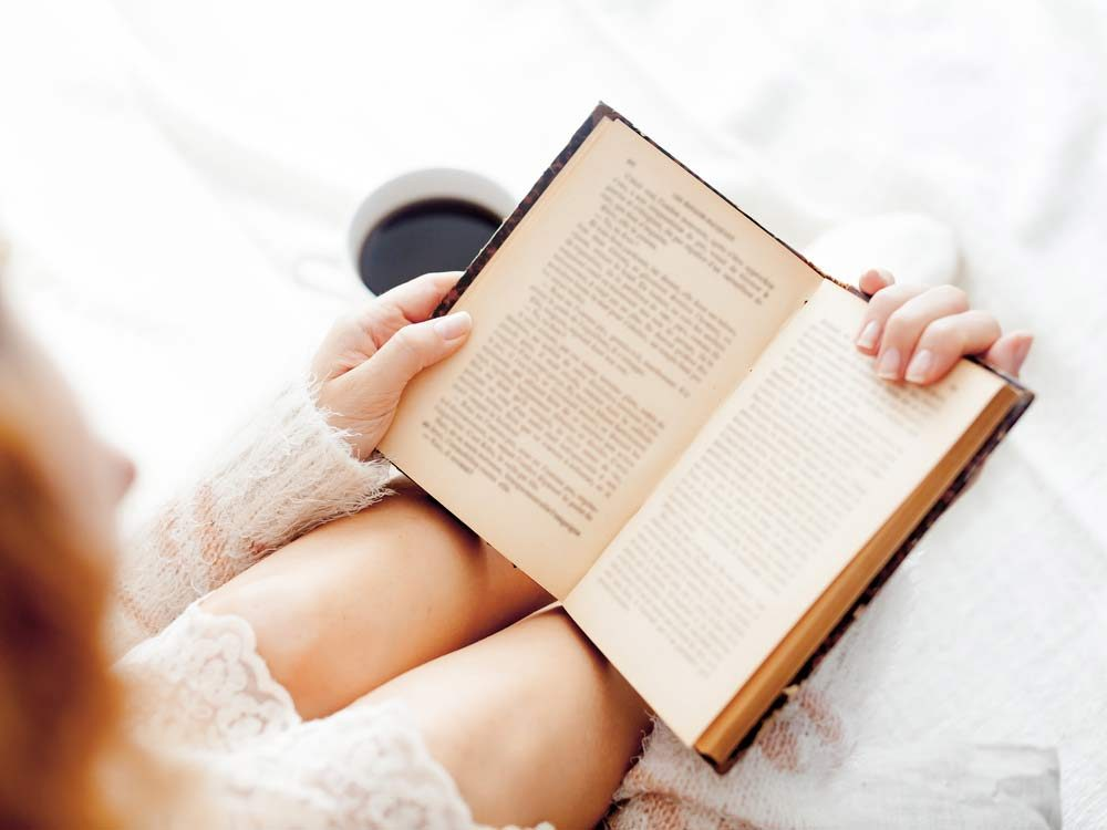 Woman reading a book in bed with a cup of coffee