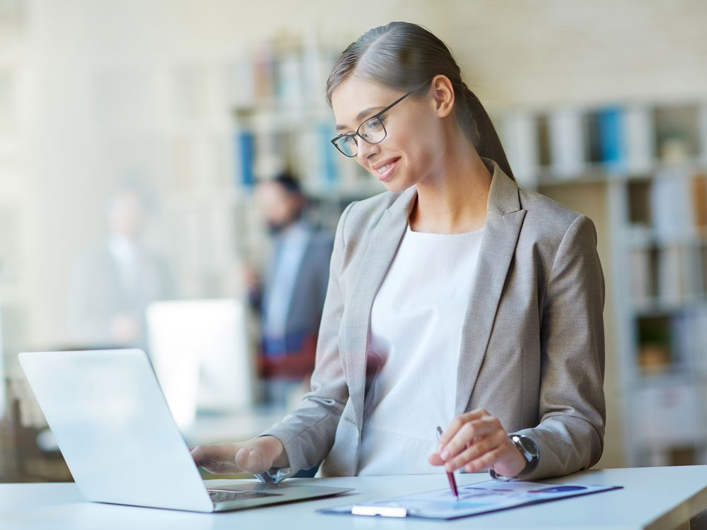 Businesswoman happily working at her desk in office