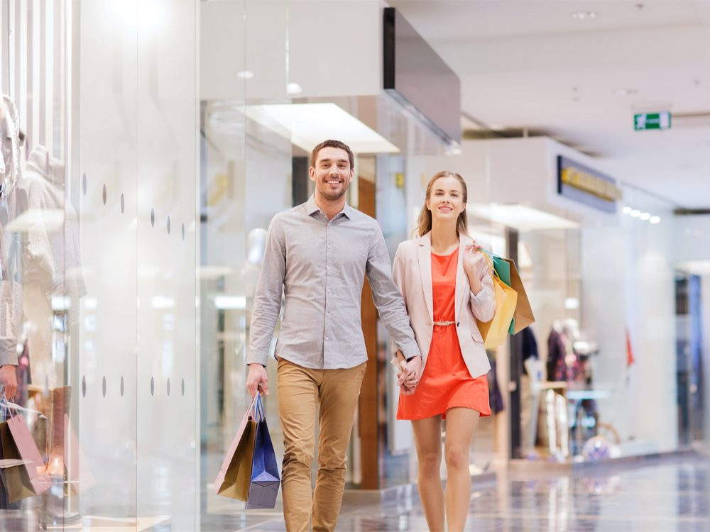 Couple walking through mall with shopping bags