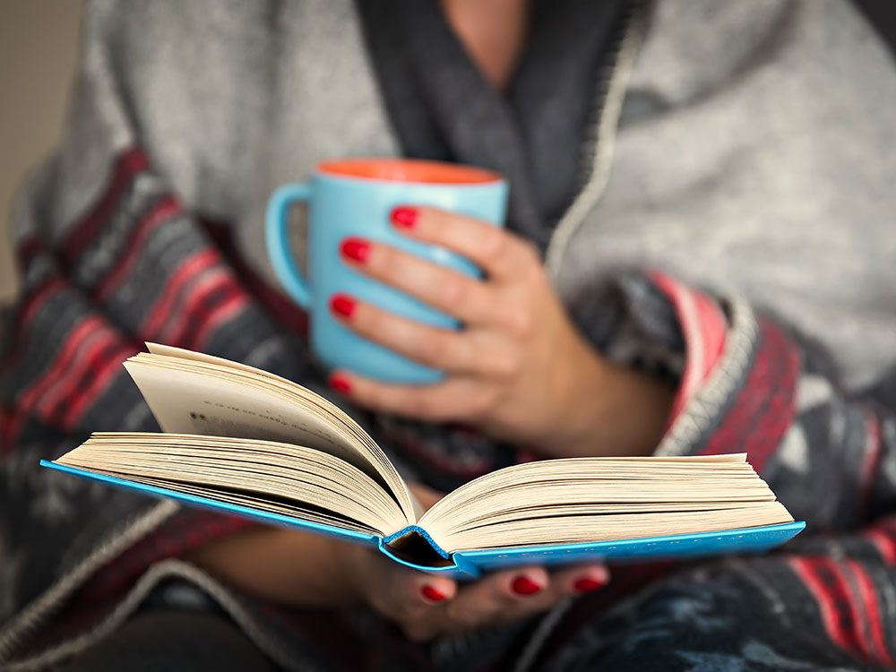 Woman reading book while under blanket