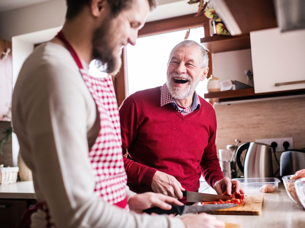 Father and hipster son prepping food in kitchen