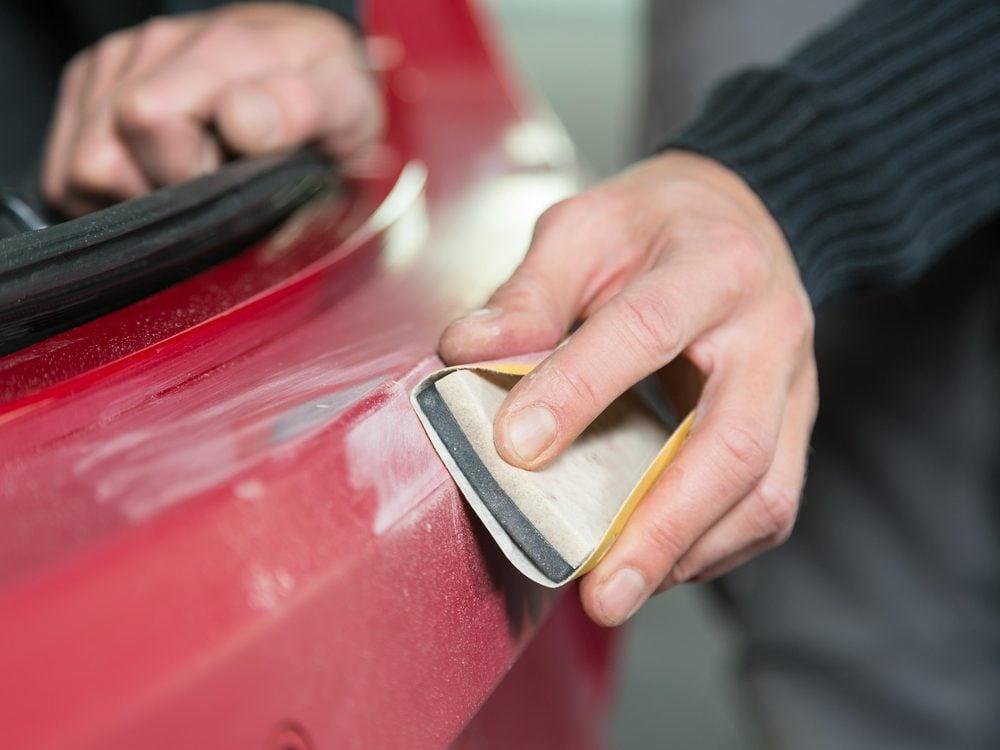 Preparing car varnish with sandpaper