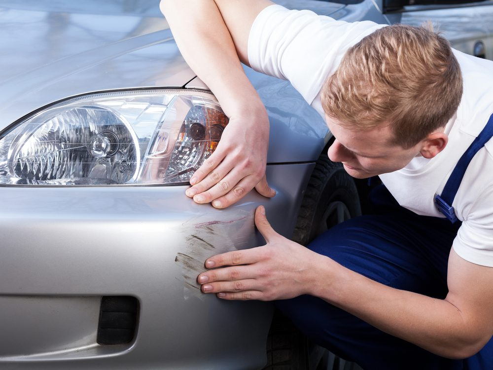 A man trying to fix a scratch on his car's body