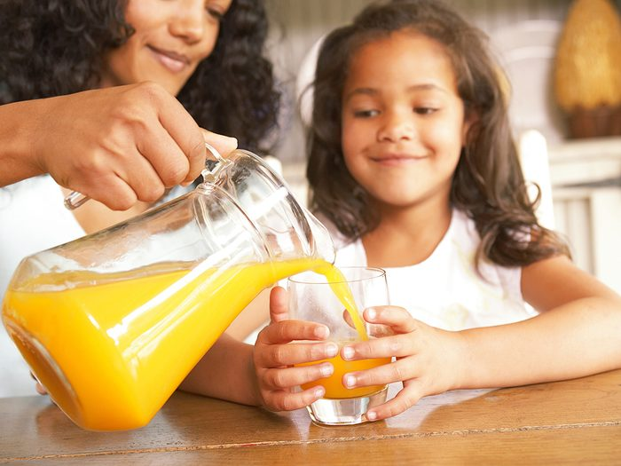 Dental facts Canada - Mother pouring fresh orange juice from a jug for her daughter seated at a wooden table in the kitchen